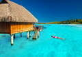 Young woman swimming in tropical lagoon next to overwater villa - PhotoDune Item for Sale