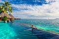 Woman in the infinity pool in exotic island resort with bunalows - PhotoDune Item for Sale