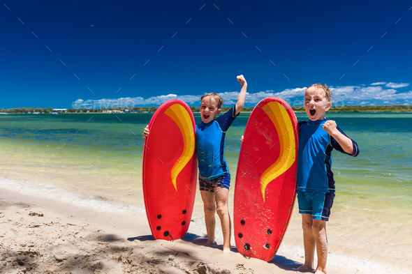 Young surfer brothers have fun on beach learning to surf - Stock Photo - Images
