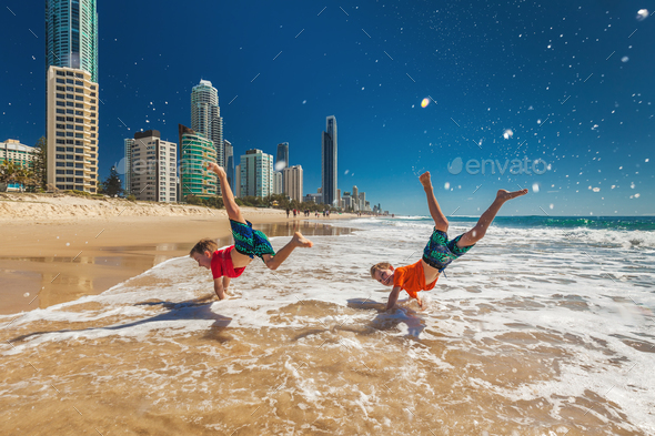 Two happy boys doing hand stands on Gold Coast beach, Australia - Stock Photo - Images