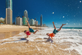 Two happy boys doing hand stands on Gold Coast beach, Australia - PhotoDune Item for Sale
