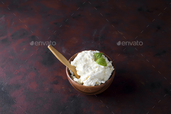 Fresh cottage cheese in a wooden bowl and spoon on - Stock Photo - Images