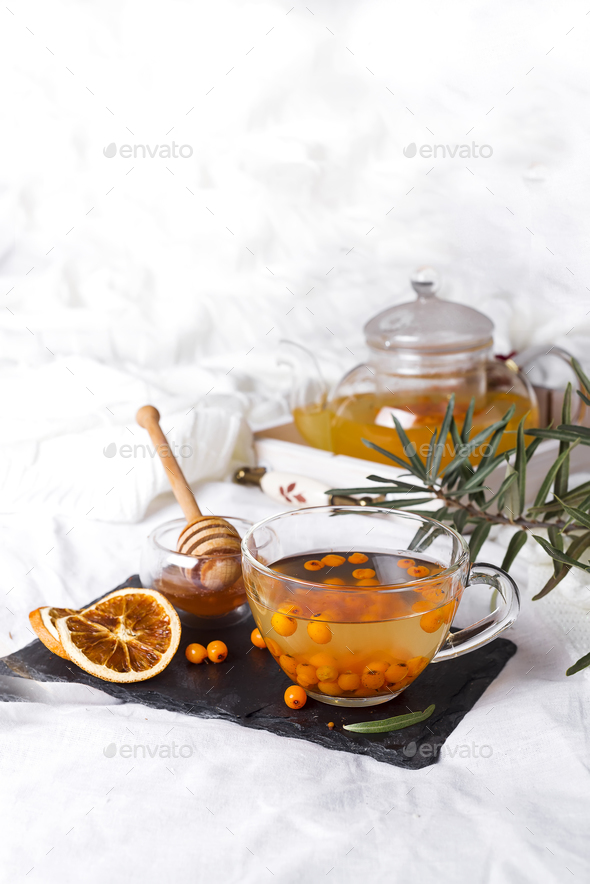 A glass teapot with sea buckthorn - Stock Photo - Images