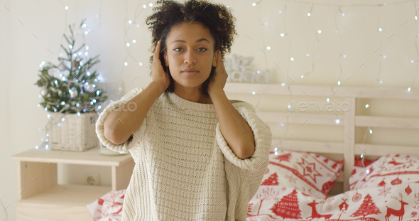 Calm young woman adusting hair in bed - Stock Photo - Images