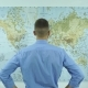 Businessman Looks at a Map of the World - VideoHive Item for Sale