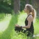 Woman Doing Yoga Outside in the Park. She Sitting on Lotus Pose