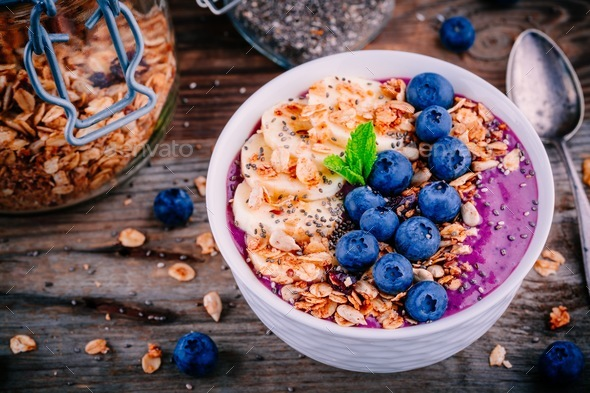 healthy smoothie bowl with granola, banana and fresh blueberries - Stock Photo - Images