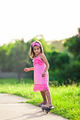 Young girl in pink dress riding on skateboard - PhotoDune Item for Sale