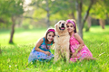 Two young girls hugging golden retriever in the park - PhotoDune Item for Sale
