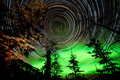Star trails and Northern lights in sky over taiga - PhotoDune Item for Sale