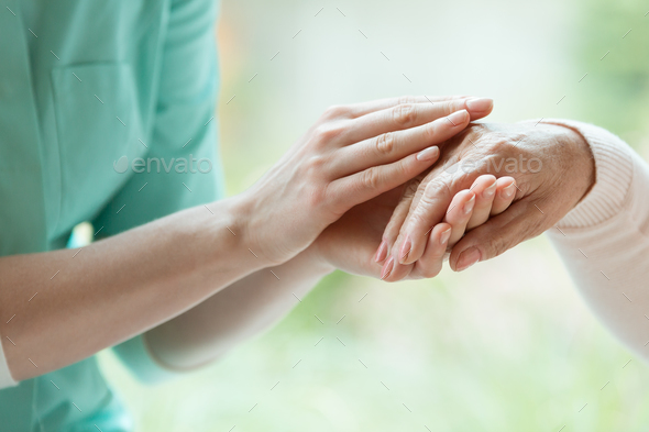 Caretaker massaging pensioner's hand - Stock Photo - Images