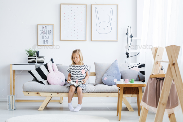 Girl reading on sofa - Stock Photo - Images