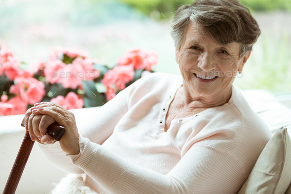 Woman with walking stick smiling - Stock Photo - Images