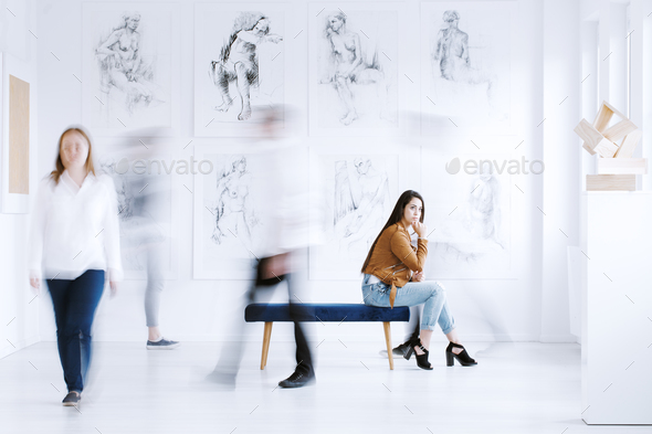 Woman looking at sculpture - Stock Photo - Images
