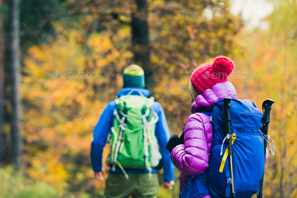 Man and woman happy couple hikers walking in autumn woods - Stock Photo - Images