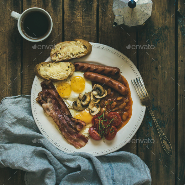 Traditional English breakfast with fried eggs, sausages, mushrooms, bacon, coffee - Stock Photo - Images