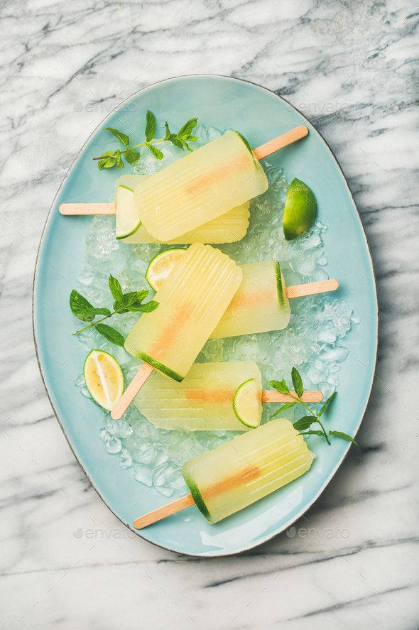 Summer lemonade popsicles with lime, mint leaves and chipped ice - Stock Photo - Images