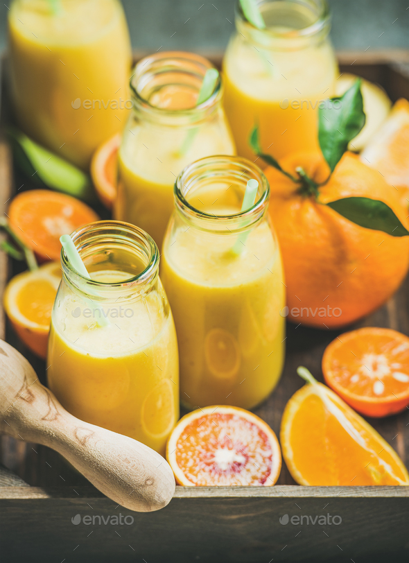 Healthy yellow smoothie in bottles in wooden box - Stock Photo - Images