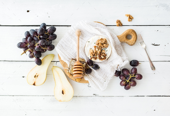 Camembert cheese with grape, walnuts, pear and honey on vintage metal plate - Stock Photo - Images