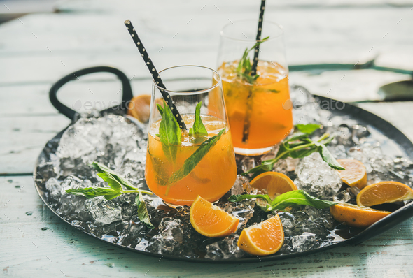 Refreshing cold alcoholic summer cocktail with orange on tray - Stock Photo - Images