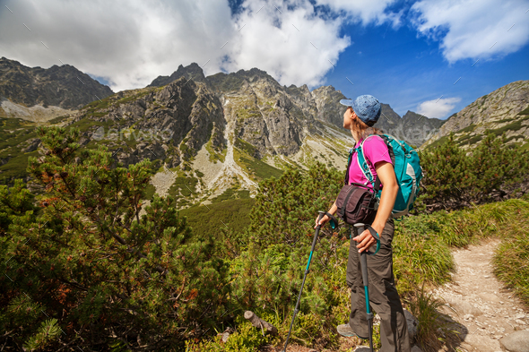 Hiking woman admiring the beauty of rocky mountains - Stock Photo - Images