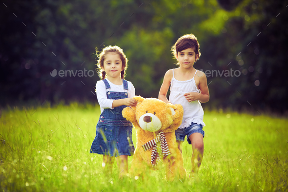 Two little girls in the grass with teddy bear - Stock Photo - Images