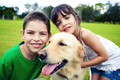 Young boy and girl hugging a golden retriever - PhotoDune Item for Sale
