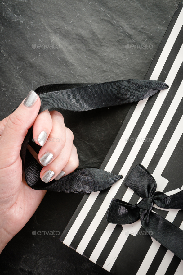 Female hand holding a package in white and black stripes with a bow close-up - Stock Photo - Images
