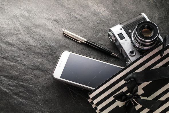 Phone, camera, pen in a black bag with white strips free space - Stock Photo - Images