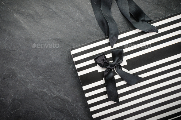 White package in black stripe with handles ribbons and black bow free space - Stock Photo - Images