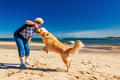Happy woman playing on the beach with golden retriever - PhotoDune Item for Sale
