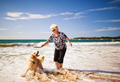 Woman playing on the beach with golden retriever - PhotoDune Item for Sale