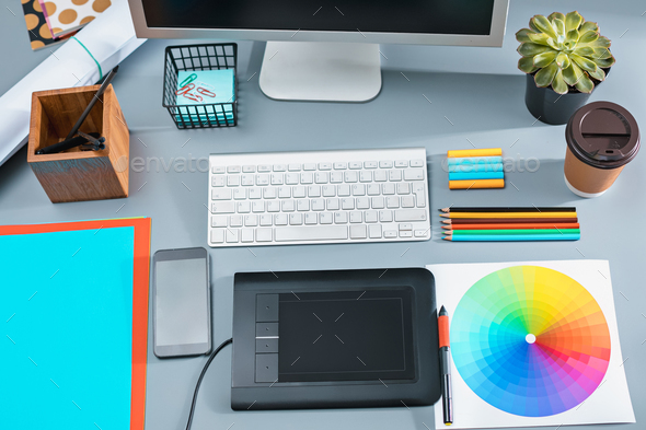 The gray desk with laptop, notepad with blank sheet, pot of flower, stylus and tablet for retouching - Stock Photo - Images
