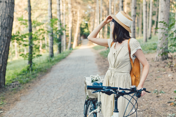 Outdoor portrait of attractive young brunette in a hat on a bicycle. - Stock Photo - Images