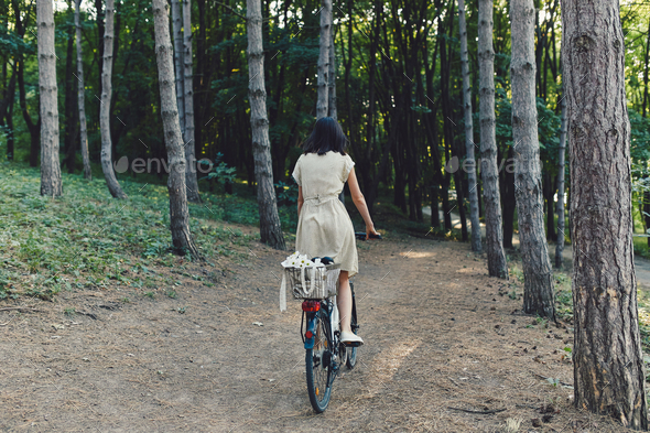Young woman against nature background with bike - Stock Photo - Images