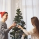 Free Download Happy young couple decorating christmas tree in cute sweaters Nulled