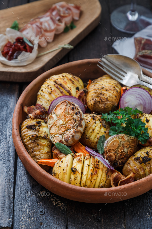 Bowl of oven roasted hassleback Potato with garlic, carrots and onion on rustic black wooden surface - Stock Photo - Images