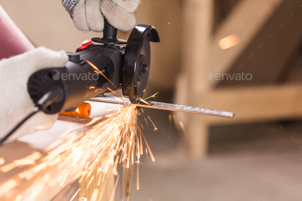 Heavy industry worker cutting steel with angle grinder - Stock Photo - Images