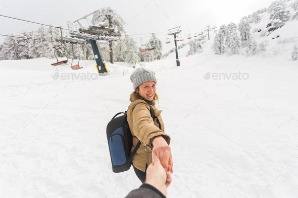 Follow me girl holding boyfriend hand in winter snow nature. Ski resort on the background - Stock Photo - Images
