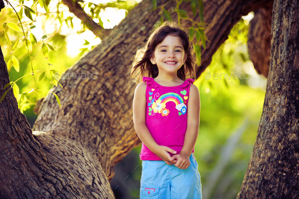 Smiling young girl standing on tree branches - Stock Photo - Images