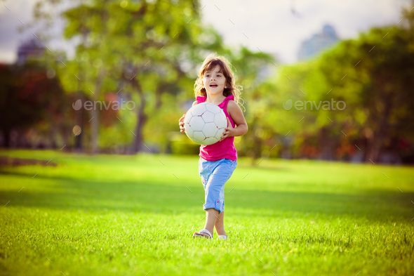 Young girl in the park holding white ball - Stock Photo - Images