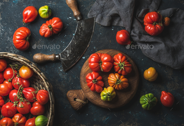 Fresh colorful ripe heirloom tomatoes in basket and wooden board - Stock Photo - Images