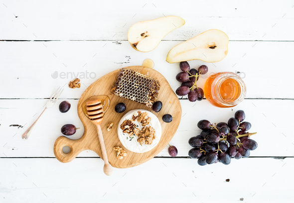 Camembert cheese with grape, walnuts, pear and honey - Stock Photo - Images
