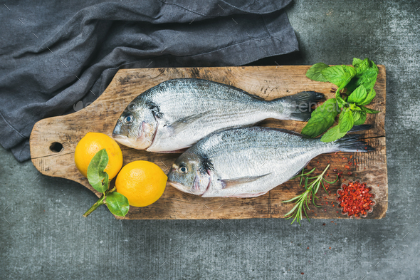Uncooked sea bream or dorado fish with lemon - Stock Photo - Images