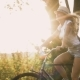 a Young Blonde Girl in Pants on Retro Bike Going Down the Road in the Field - VideoHive Item for Sale