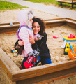 Mother playing with her daughter in a sandbox - PhotoDune Item for Sale