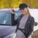 Trendy Woman in Black Showing Keys From New Expensive Car