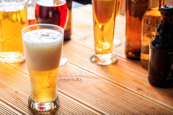 A wooden pub counter, focus on a full frosty glass of beer - Stock Photo - Images