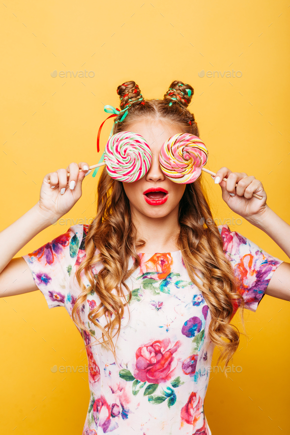 Young girl on the yellow background holding sweets - Stock Photo - Images