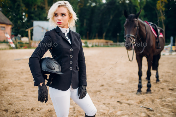 Woman with helmet in hands poses against horse - Stock Photo - Images